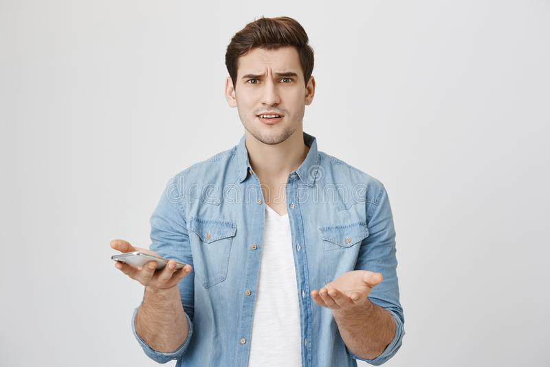Portrait of attractive young adult with perplexed and confused expression, holding smartphone and showing with gestures. That he don`t understand something royalty free stock image