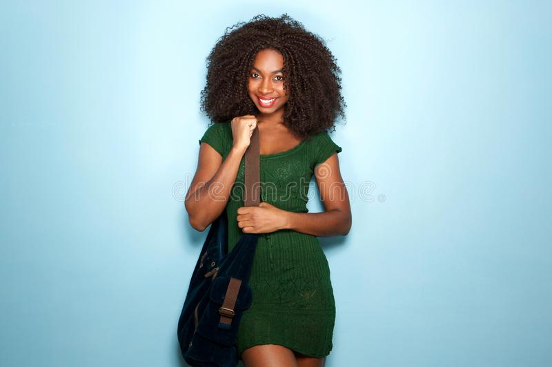 Attractive young african american woman in beautiful dress and handbag on blue background stock photos