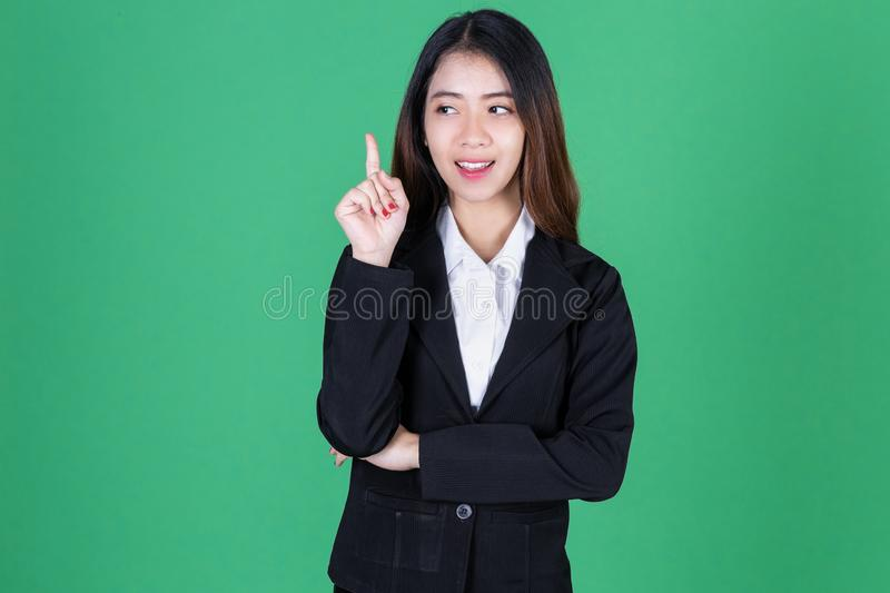Portrait of attractive young Asian business woman having idea posing on green  background royalty free stock image