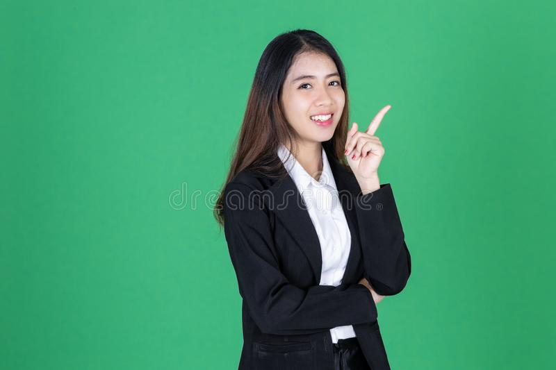 Portrait of attractive young Asian business woman having idea posing on green isolated background stock image