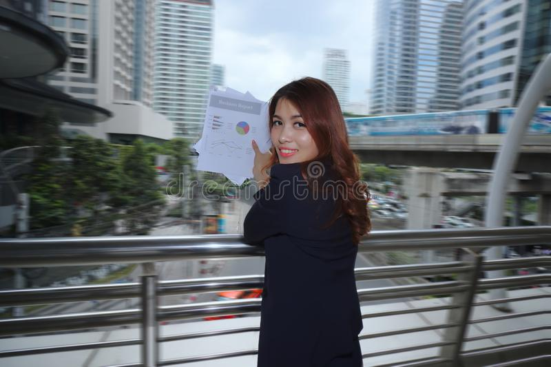 Portrait of attractive young Asian business woman holding charts or paperwork at outside office. royalty free stock photography