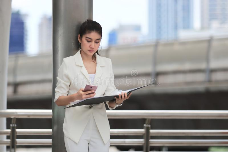 Portrait of attractive young Asian business woman holding mobile smart phone and ring binder at outside office royalty free stock photo