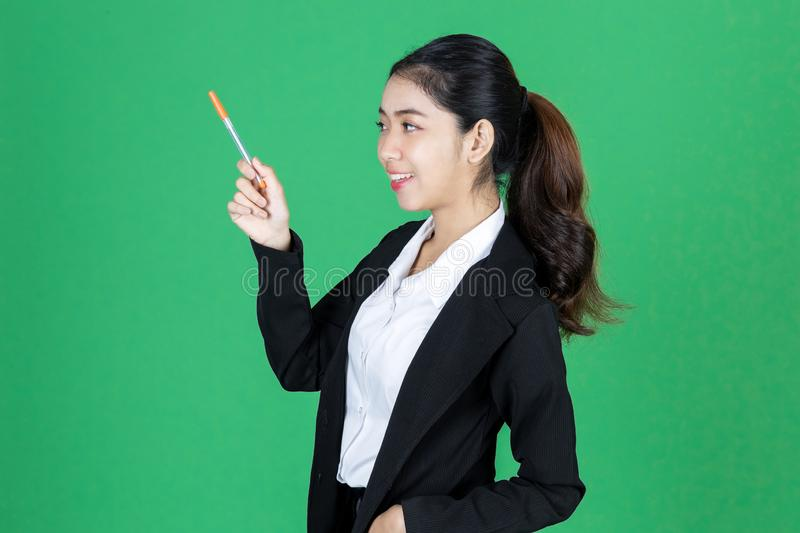 Portrait of attractive young Asian business woman holding pen and having idea posing on green  background royalty free stock photo