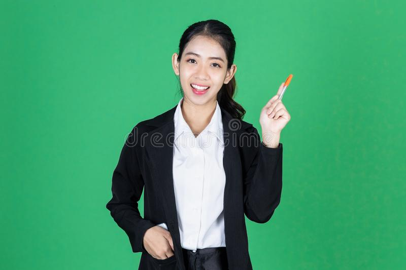 Portrait of attractive young Asian business woman holding pen and having idea posing on green isolated background stock image