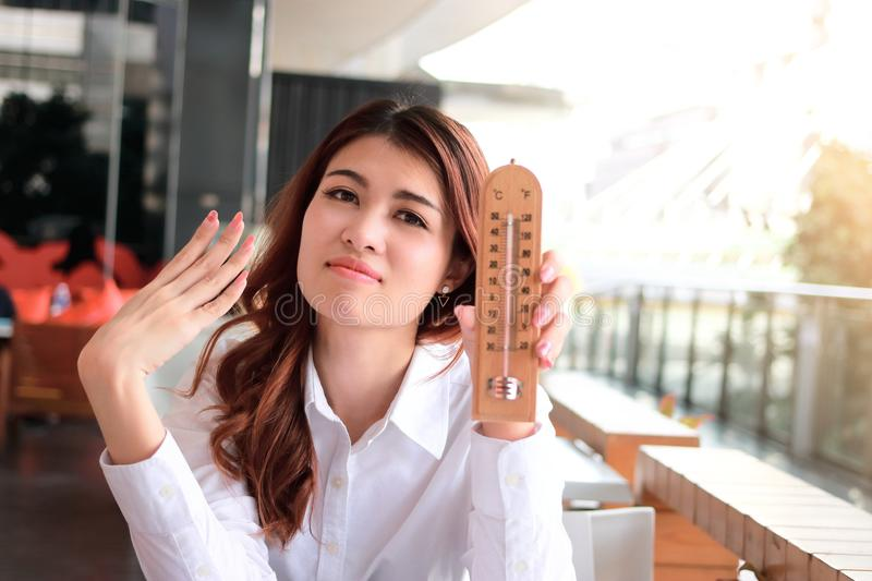 Portrait of attractive young Asian woman holding thermometer and feeling so hot. Summer time royalty free stock image