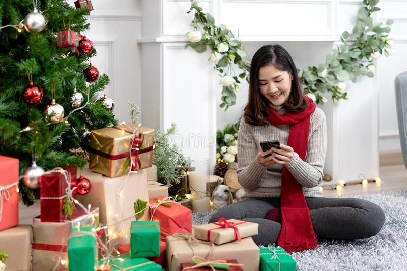 Portrait of attractive young asian woman or teenage girl smiling and looking at smartphone mobile chatting or using social media stock photo