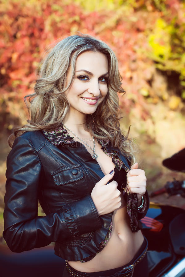 Portrait of an attractive young blond woman biker posing on her stock image