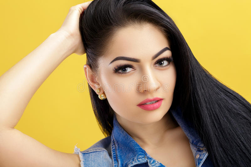 Portrait of attractive young brunette woman in denim vest on yellow background. Portrait of attractive young brunette woman in a denim vest on a yellow stock photos