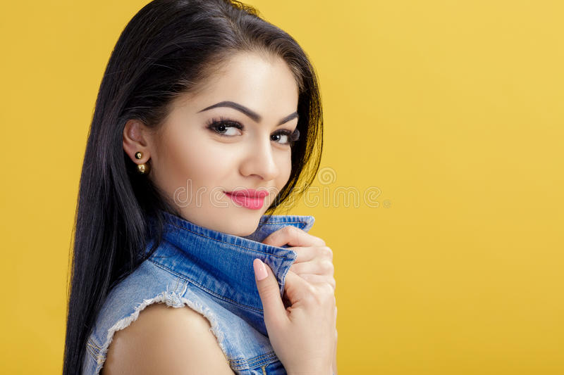 Portrait of attractive young brunette woman in denim vest on yellow background. Portrait of attractive young brunette woman in a denim vest on a yellow royalty free stock photos
