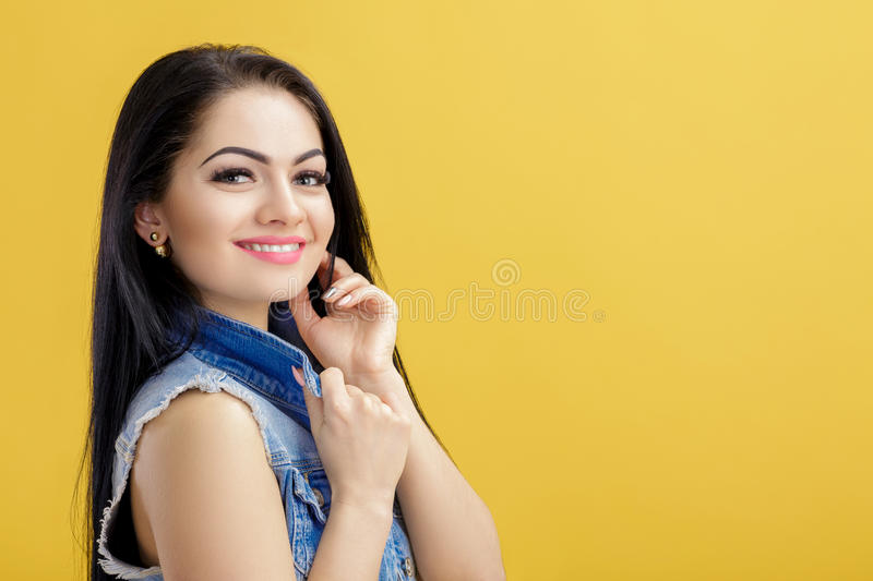 Portrait of attractive young brunette woman in denim vest on yellow background. Portrait of attractive young brunette woman in a denim vest on a yellow royalty free stock photography