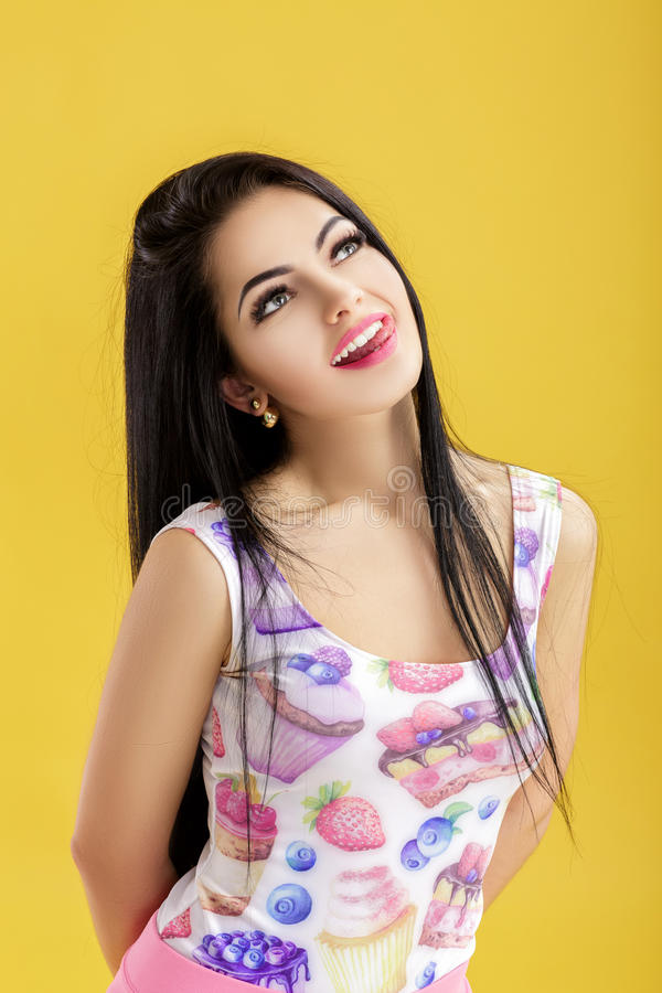 Portrait of attractive young brunette woman in pink tank top on yellow background. funny girl with dark hair stock photography