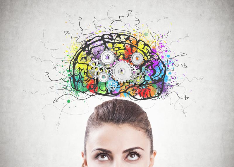 Pensive woman s head, cog brain. Portrait of an attractive young brunette woman wearing a brown blouse and looking upwards at a colorful brain sketch with cogs