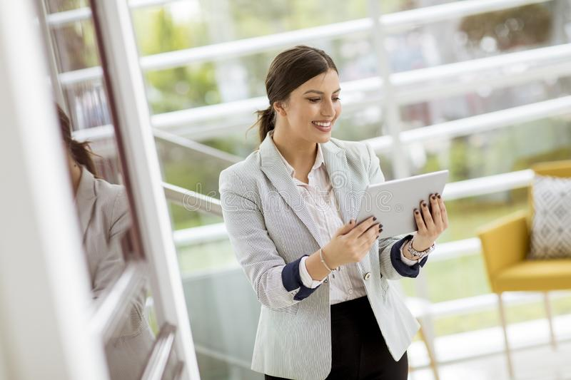 Portrait of attractive young business woman smiling confidently and working online with a digital tablet while standing in a stock photo