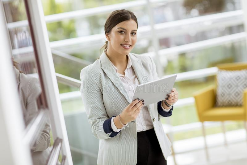 Portrait of attractive young business woman smiling confidently and working online with a digital tablet while standing in a stock images