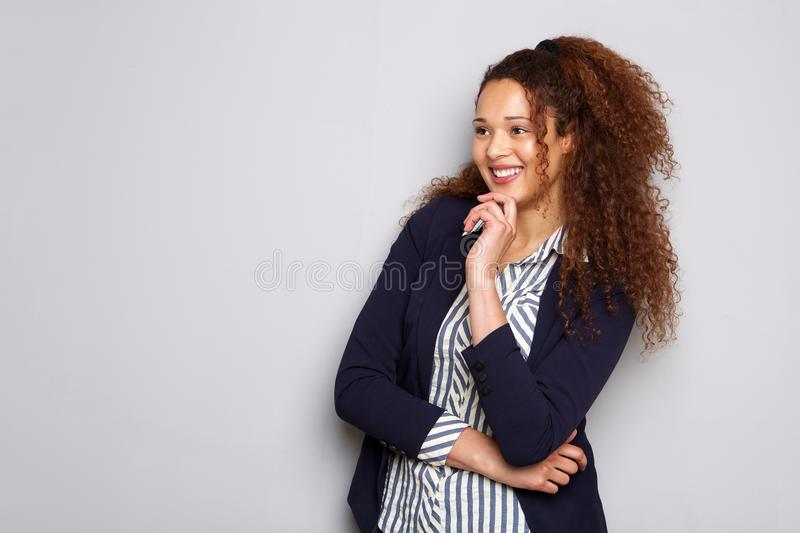 Attractive young businesswoman with curly hair smiling against gray background. Portrait of attractive young businesswoman with curly hair smiling against gray royalty free stock photo