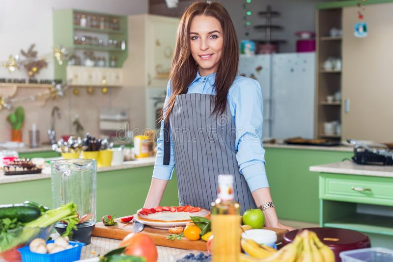 Portrait of attractive young cook wearing apron posing standing at workplace with fresh fruit and vegetables on table stock photos