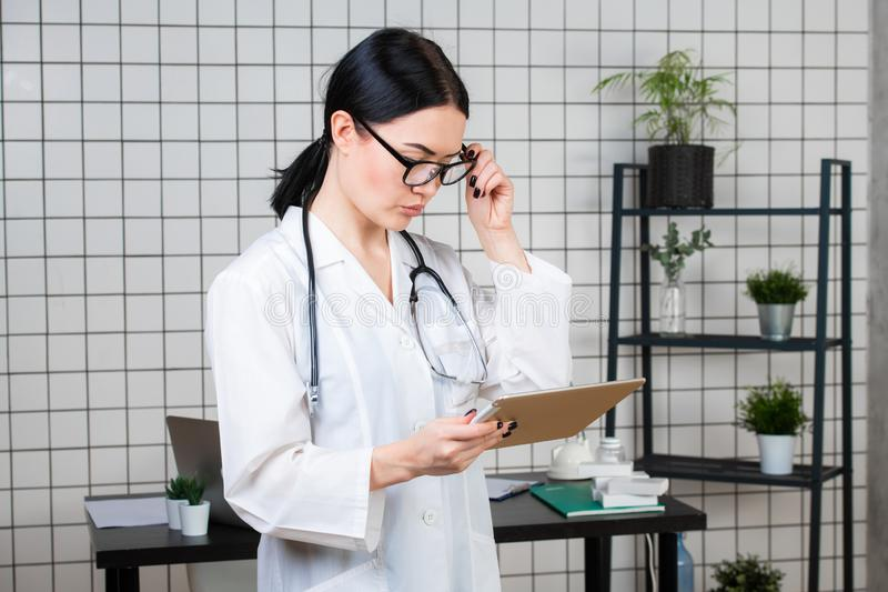 Portrait of an attractive young female doctor or nurse wearing glasses in white uniform with stethoscope holding tablet stock photos
