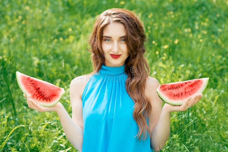 Portrait of attractive young girl holding two slices of juicy watermelon royalty free stock photo