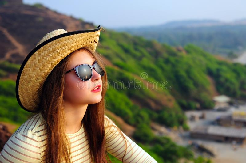 Portrait of an attractive young girl with long hair in straw hat and sunglasses on background of green hills. Selective focus royalty free stock photo