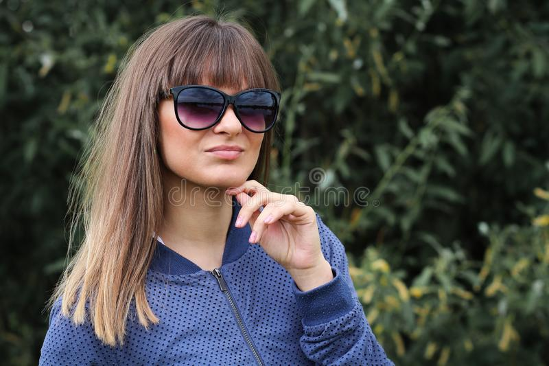 Portrait of attractive young girl in park against green plants. Pretty girl in sunglasses. Fashionable teen . stock image