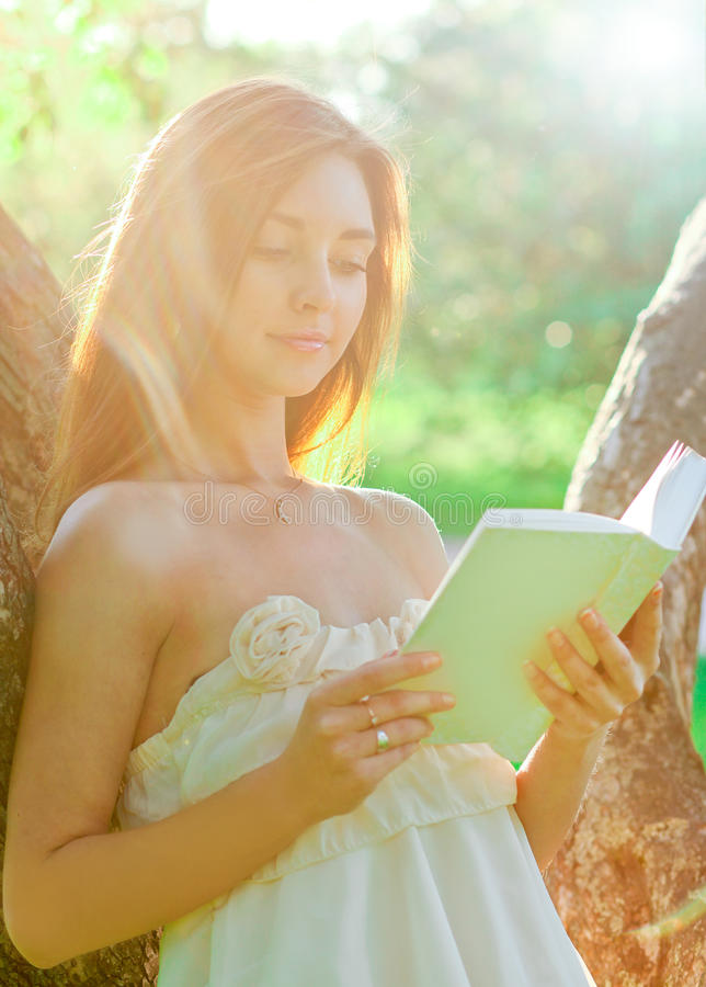 Portrait of attractive young girl reading book stock photo