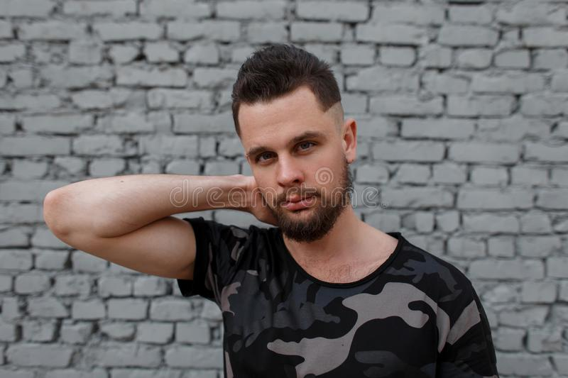 Portrait of attractive young handsome man with a stylish hairstyle and brutal beard in a stylish camouflage military t-shirt royalty free stock photos