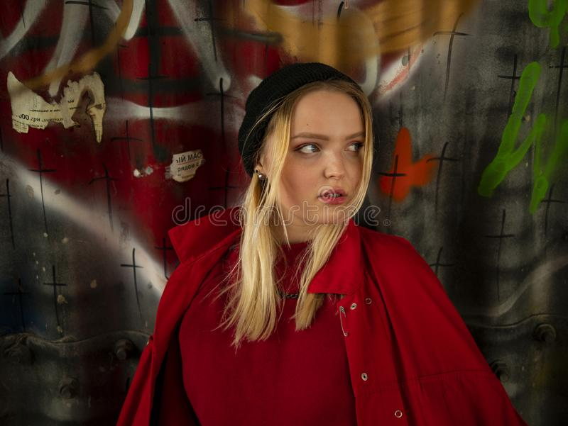 Portrait of an attractive young hipster girl in a knitted hat against the wall with inscriptions royalty free stock image