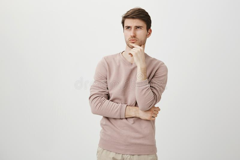 Portrait of attractive young man with bristle looking up while touching chin and thinking about something, standing over. Gray background in trendy pullover stock images