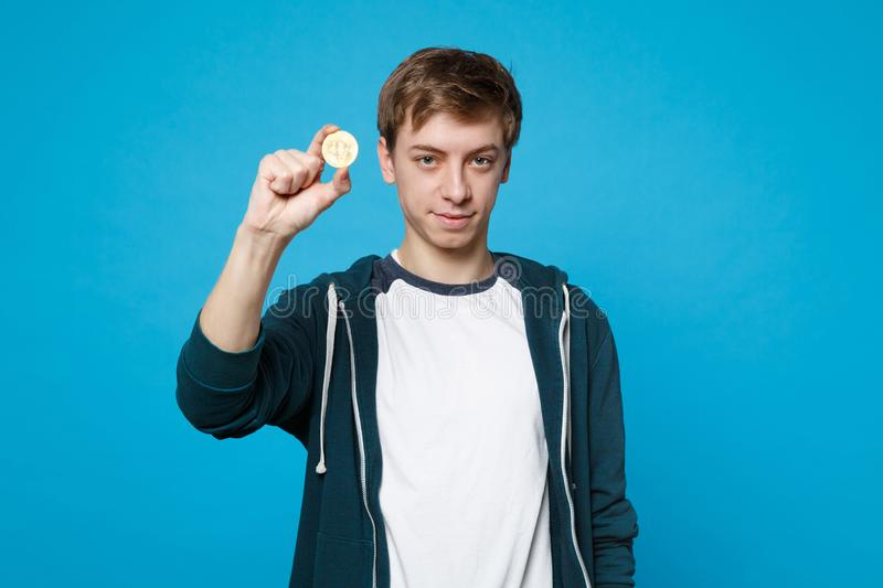 Portrait of attractive young man in casual clothes holding bitcoin, future currency isolated on blue wall background stock photo