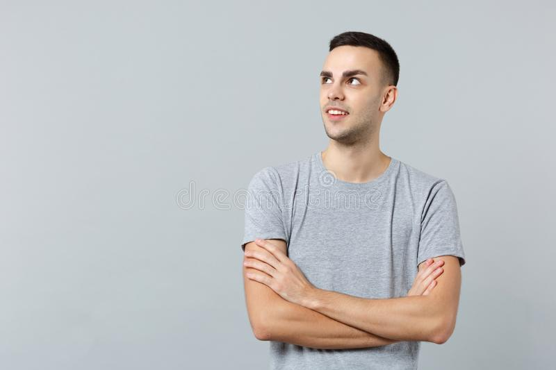 Portrait of attractive young man in casual clothes looking aside and holding hands crossed isolated on grey wall stock image