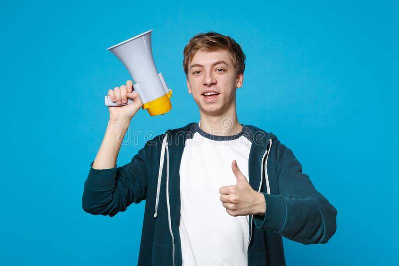 Portrait of attractive young man in casual clothes showing thumb up holding megaphone isolated on blue wall background royalty free stock photos