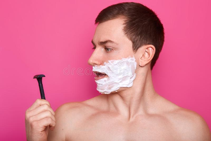 Portrait of attractive young man with foam all over his face looking at razor while standing with serious facial expression, model stock images