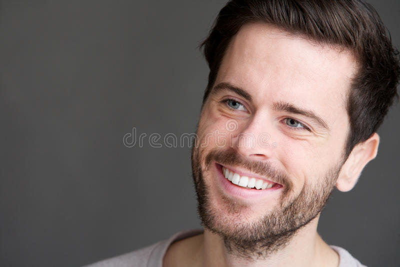 Download Portrait Of An Attractive Young Man Smiling On Gray Background Stock Photo - Image of blue, caucasian: 34256230