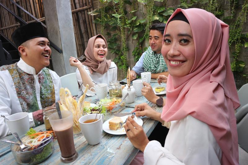 Portrait of attractive young muslim woman looking at camera while other enjoying meal stock photos
