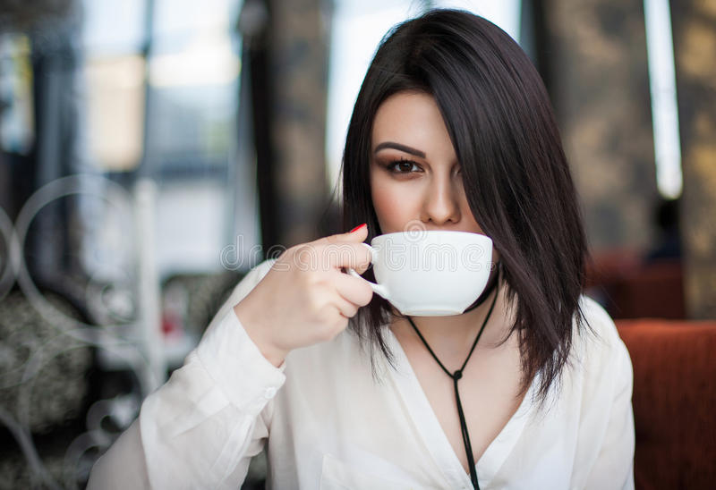 Portrait of attractive young single brunette female having thoughtful dreamy look, holding mug, enjoying good cappuccino alone du stock photography