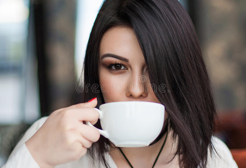 Portrait of attractive young single brunette female having thoughtful dreamy look, holding mug, enjoying good cappuccino alone du royalty free stock photography