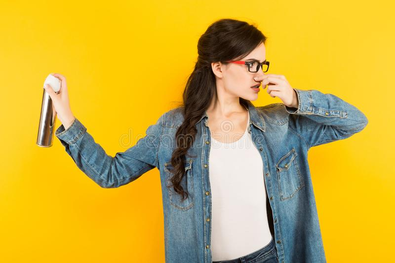 Young woman with sprayer against unpleasant smell royalty free stock photo