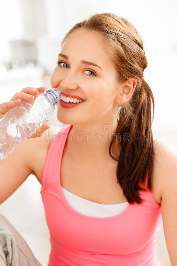 Portrait of attractive young woman drinking water at gym. Portrait of attractive young woman drinking water exercising at gym royalty free stock photo