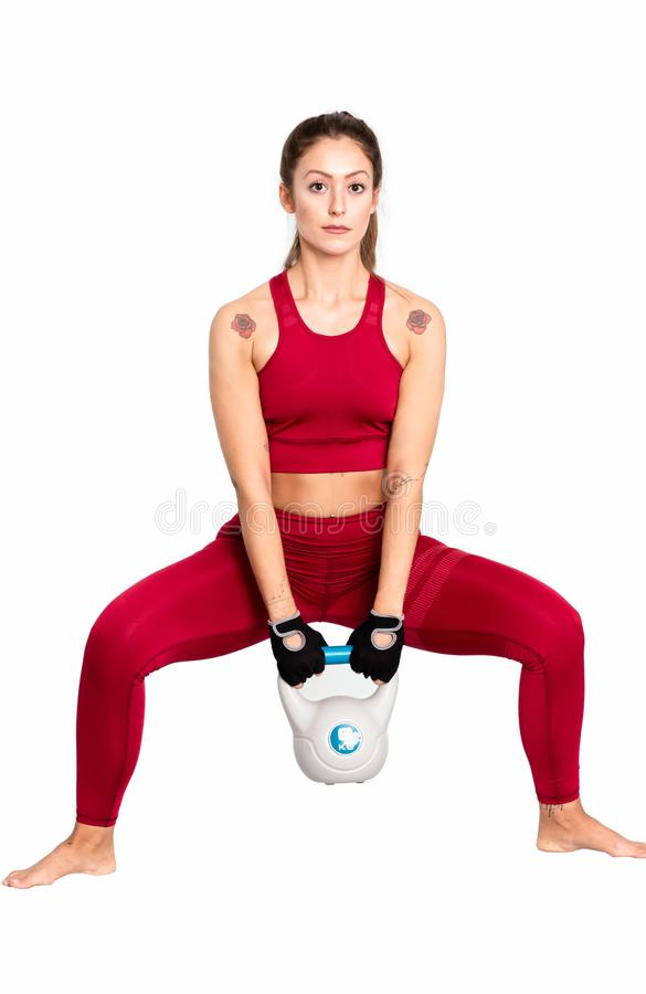 Portrait of attractive young woman focused on workout with kettlebell  - Image royalty free stock photography