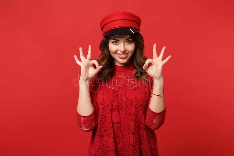 Portrait of attractive young woman in lace dress, cap looking camera showing OK gesture isolated on bright red wall. Background in studio. People sincere stock photo