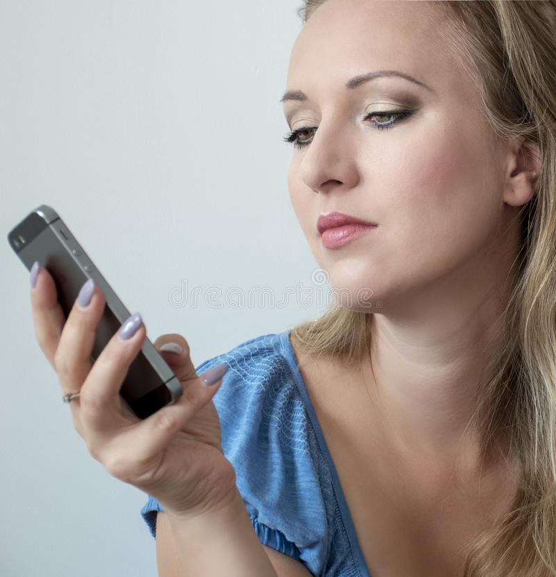 Portrait of attractive young woman looking on the phone. Pretty woman with green eyes and long blonde hair holding smartphone royalty free stock images