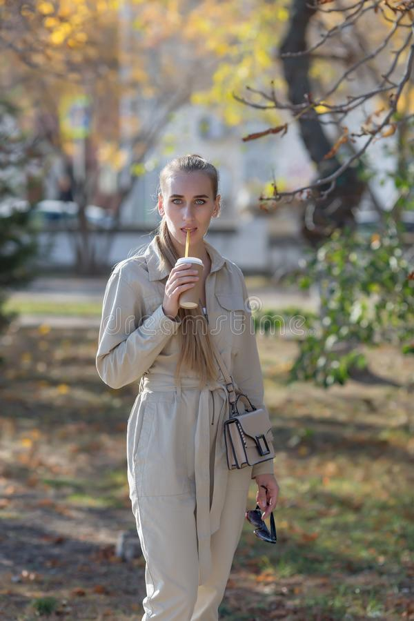 Portrait of an attractive young woman in overalls in autumn park stock images