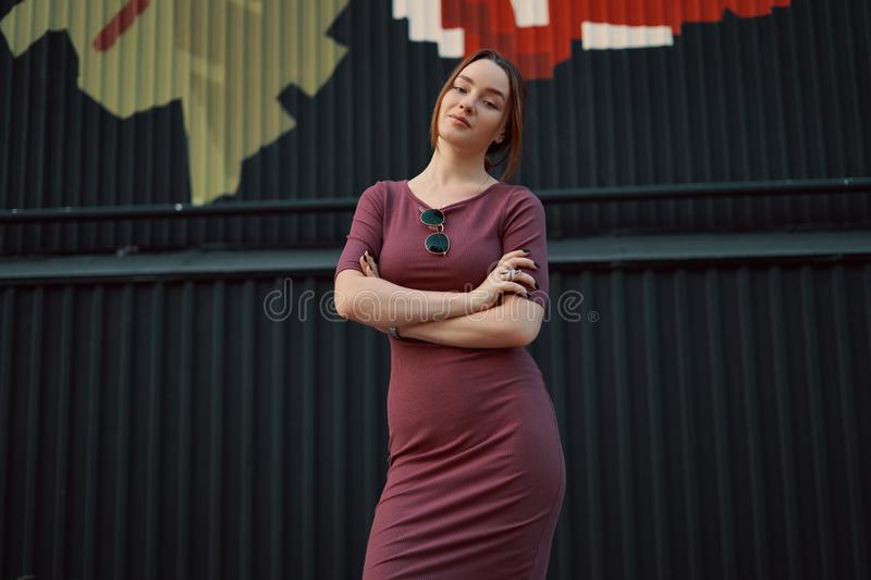 Portrait of attractive young woman posing against dark wall royalty free stock photography