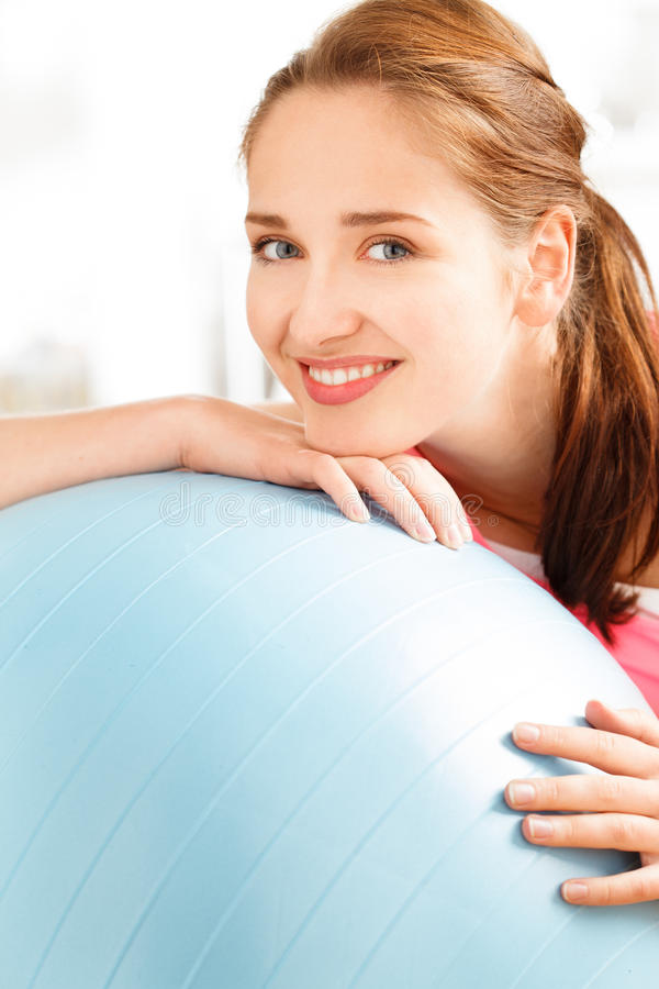 Portrait of attractive young woman relaxing fitness ball at gym. Smiling stock photography