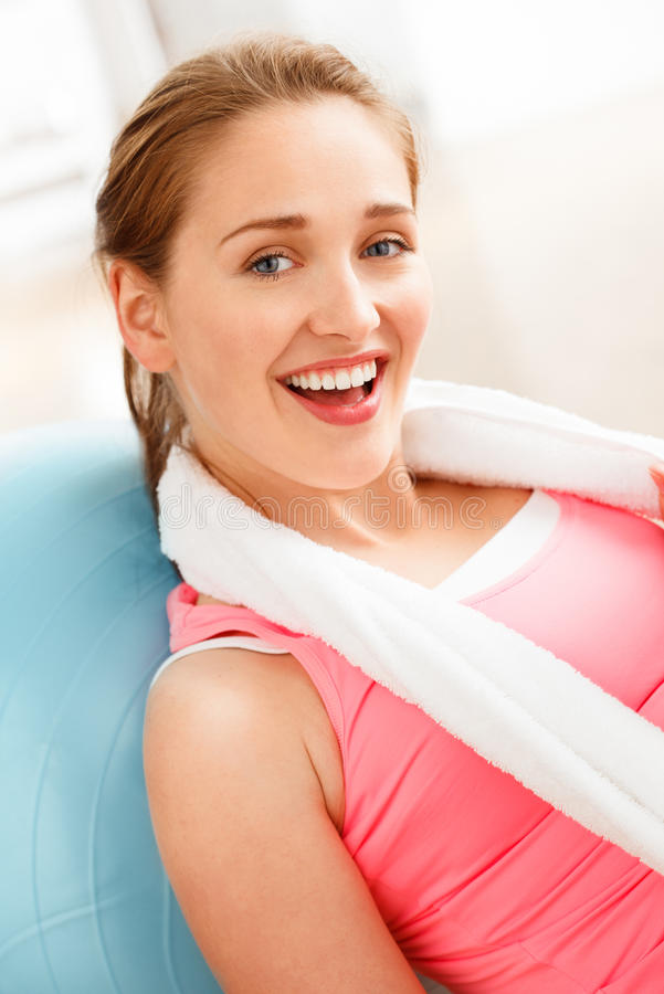 Portrait of attractive young woman relaxing fitness ball at gym. Smiling stock photo