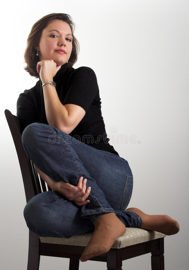 Portrait of an attractive young woman sitting on a chair. Portrait of an attractive young woman posing on a chair; dark hair, dark eyes, dressed in dark blouse royalty free stock photography