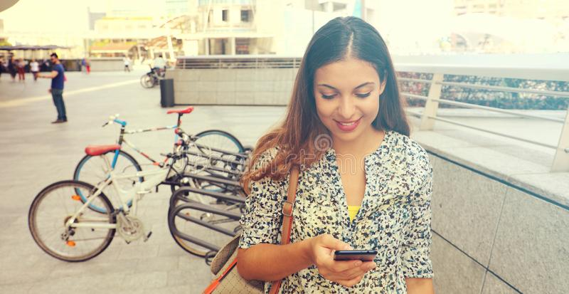 Portrait of an attractive young woman using a smartphone. Executive working with a mobile phone in the street. Panoramic banner v. Iew. Desatured retro filtered royalty free stock photography