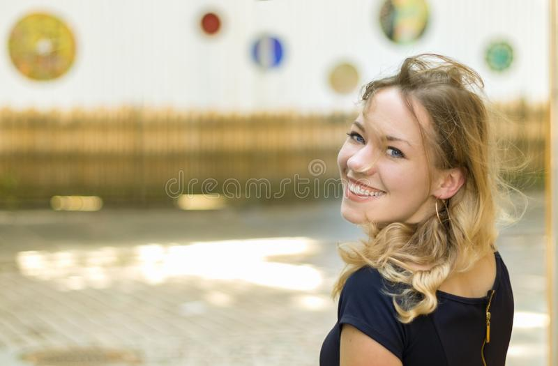 Portrait of an austrian young blonde woman turning her head, smiling stock photography
