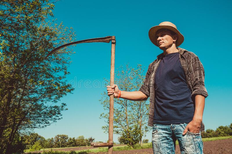 Portrait authentic rural farmer with scythe. Agriculture worker. Farm implements. Rustic background. Work countryside. Brutal. Country man in hat. Manual labor royalty free stock photo