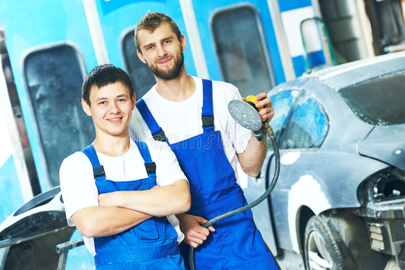 Portrait of auto mechanic workers with power polisher machine. Portrait of two smiling auto mechanic workers with power buffer machine at automobile repair and stock image